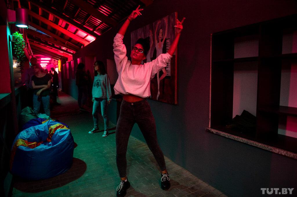 Хостес Таня танцует на фоне картины Сергея Савича